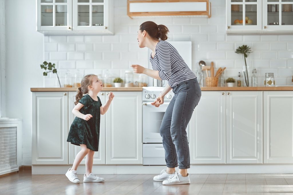 Mother dancing at home with daughter